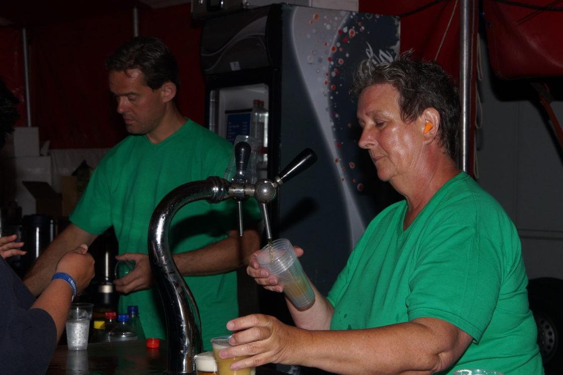 Twee personen staan achter een bar. De ene tapt een biertje