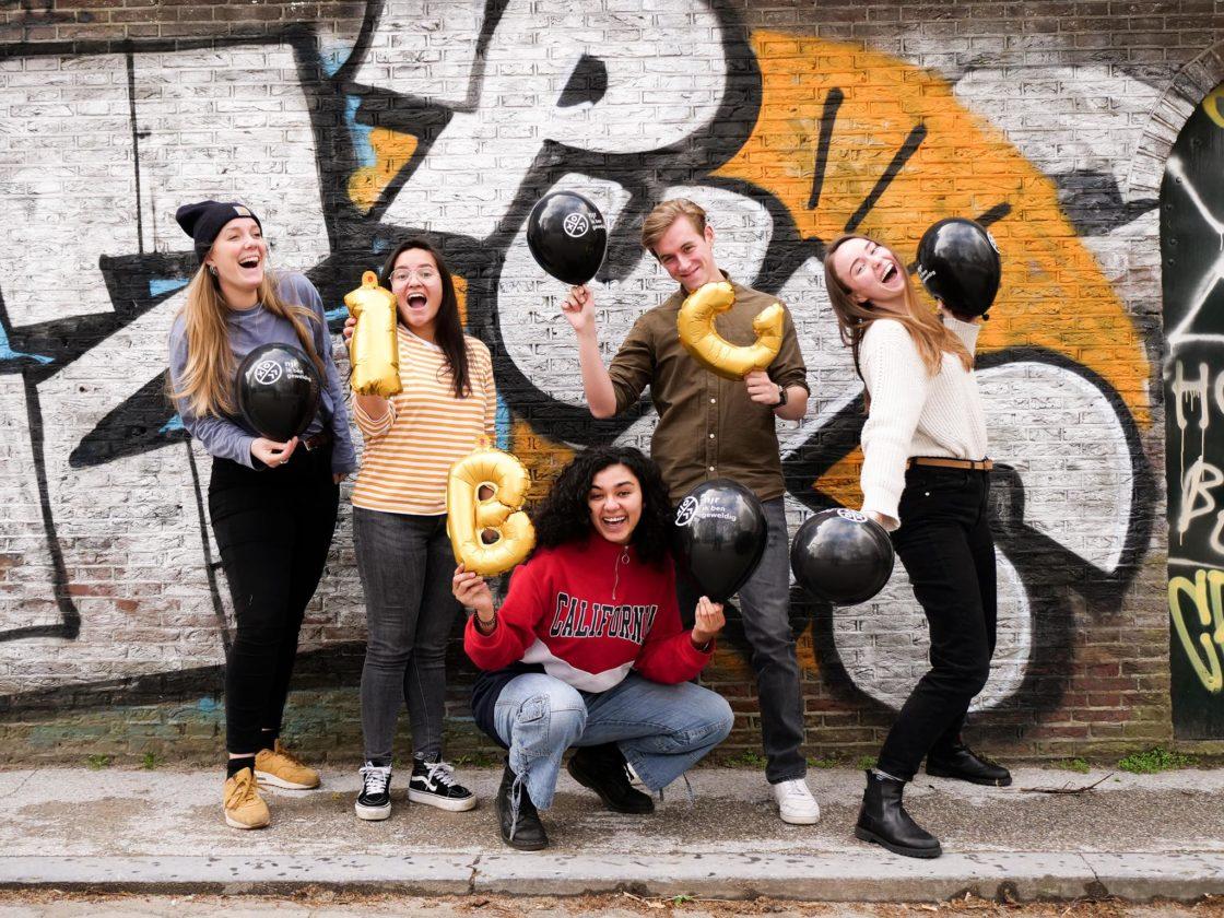 Werknemers van 'Ik ben geweldig'. Ze houden de letters I, B, en G vast.
